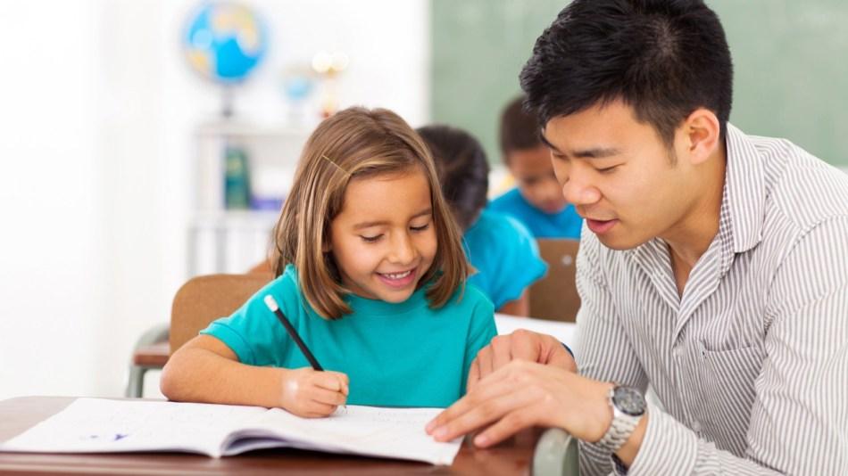 preschool teacher helping little girl with class work